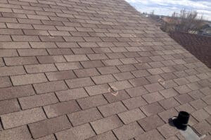 Close up of an asphalt roof with broken shingles circled did not extend roof life